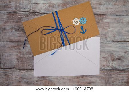 Kraft envelope tied with blue ribbon steering wheel an anchor and blank sheet of paper. Space for your text
