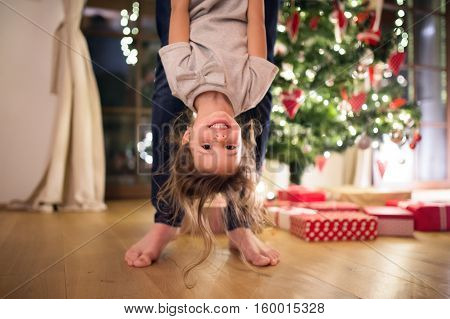 Unrecognizable young father with his little daughter at decorated Christmas tree together, holding her upside down.