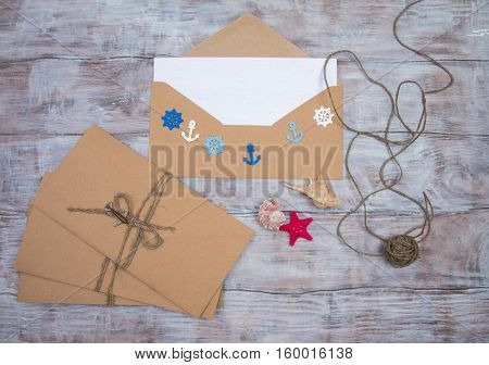 Kraft envelopes decorated with shells and ornaments in marine style on wooden background. Letters from travel. Space for your text
