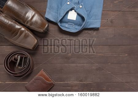 Elegant Set: Brown Men's Shoes, Brown Leather Belt, Blue Shirt, Brown Wallet, On The Wooden Backgrou