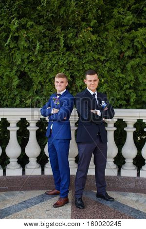 Funny groom and witness in stylish costumes posing in the photo