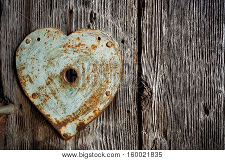 Rusty old trim on keyhole in shape of heart on old wooden door.