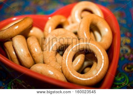 Close-up glazed bagels on red plate in shape of heart on colored background.
