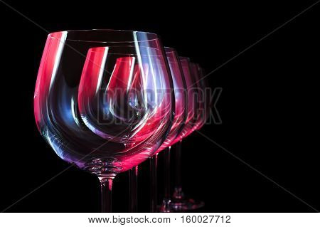 Nightclub wine glasses lit by red, blue, lilac party lights, nightlife, five object in row isolated on black background