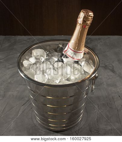 Bottle of Champagne in bucket with ice on black background