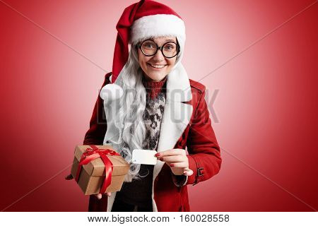 Mrs Claus happily smiling with gray hairs, weraing Santa hat, traditional sweater, round glasses and red warm coat holds beautiful craft box with holiday christmas gift inside and name tag on it, looking on camera.