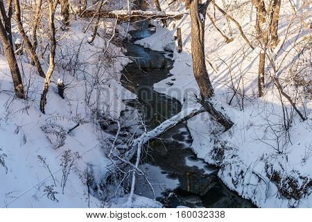 Scenic view with the narrow winding river with snow on the banks and trees on a sunny winter day
