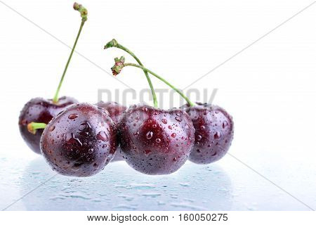 Several cherries with water drops and their reflection on glass