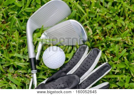Golf irons and ball with leather glove on the fairway grass
