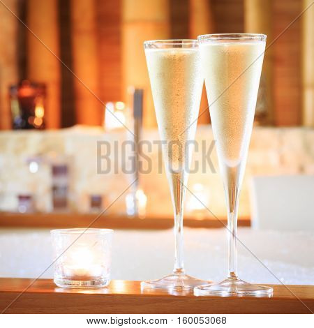 Two Glasses Of Champagne With Candle Near Jacuzzi. Valentines Background. Romance Concept