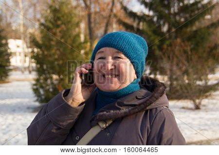 Portrait of mature woman talking on phone outdoor. Senior lady smiling and talking on the phone in park at winter sunny day, horizontal