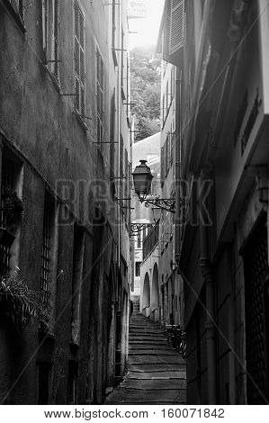 Beautiful view of scenic narrow alley street with historic traditional houses in an old town in Europe with blue sky and clouds in summer sunny day with retro vintage black and white effect