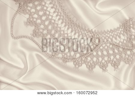 Smooth elegant golden silk or satin with pearls and lace can use as wedding background. In Sepia toned. Retro style