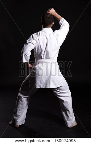 Karate man in a kimono in fighting stance on a black background.