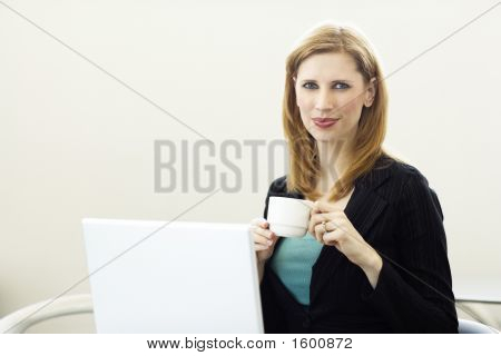 Businesswoman With Laptop And A Cup Of Coffee