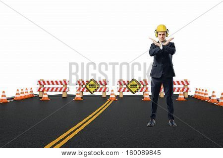 Businessman in yellow helmet and headphones standing on the road under construction with his arms crossed in stop gesture. Road repair service. Under construction. Construction site.