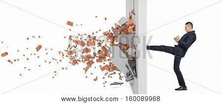 Businessman kicking hard the wall and crush it, side view. Overcoming obstacles. Business issues. Economic development.