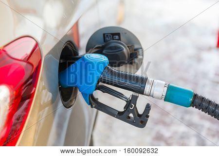 Gas pump nozzle in fuel tank of anew car, refuel