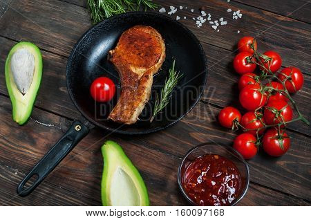 Steak in frying pan avocado and cherry tomatoes on table.
