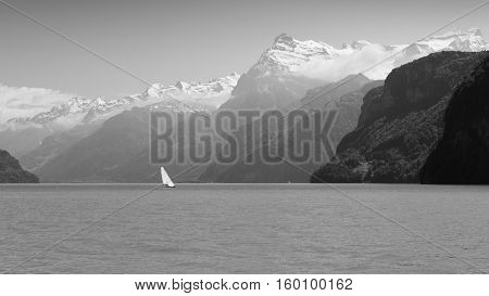 Grandiose mountain landscape. Mountain tops in the snow. Steamship floats on the lake. Black and white.