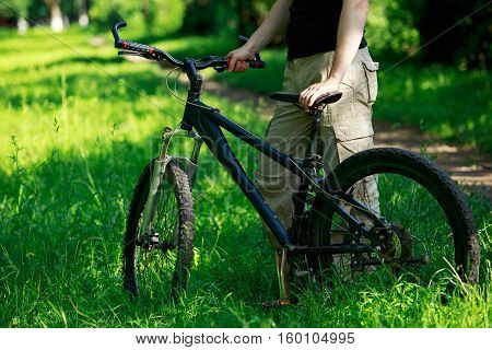 Young man riding a mountain bike in the woods