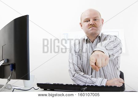 Bossy mature businessman pointing at computer desk in office. Angry and furious leader.