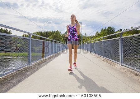 Beautiful young slim blonde woman running or jogging on a bridge over a lake. Happy and focused workout.