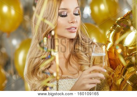 portrait of blond young woman between golden balloons. New Year concept