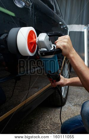 the man is polishing a car in garage