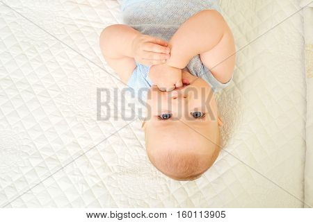 Baby boy looking into the eyes while lying on a white background. Fingers in child's mouth.Top view