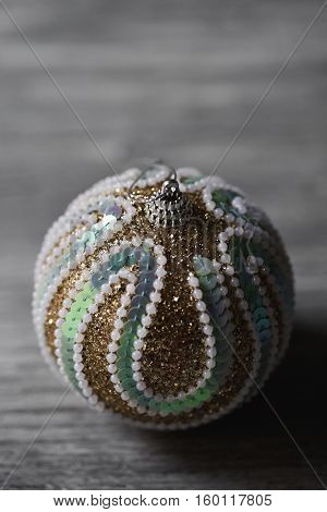 an elegant ornamented christmas ball on a gray rustic wooden surface
