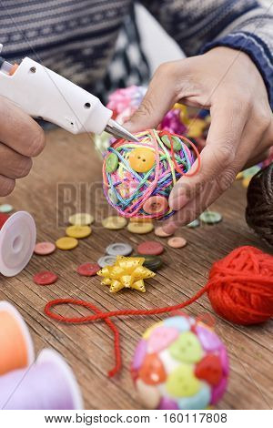 closeup of a young man making a handmade christmas ball using a hot glue gun with strings and buttons of different colors, and a pile of different haberdashery items on a rustic wooden table