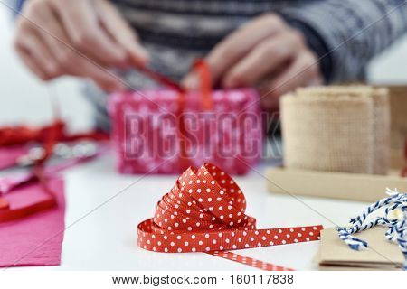 closeup of a young caucasian man tying a red ribbon around a gift wrapped in a pink paper on a white table full of boxes, and strings and ribbons of different colors