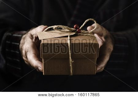 closeup of an old caucasian man holding a cozy gift tied with a jute string, a twig of holly and a paper label attached to it