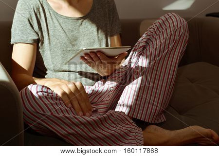 closeup of a young caucasian man in pajamas using a tablet computer seating in a couch