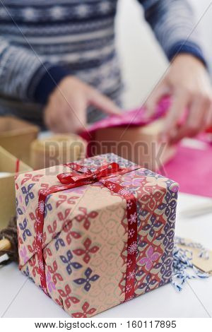 closeup of a gift and a young caucasian man wrapping a gift box on a white table full of boxes, wrapping paper and strings and ribbons of different colors