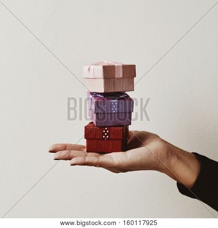 closeup of a young caucasian woman holding a balanced stack of small gifts in the palm of her hand