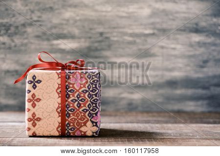 a cozy gift wrapped in a nice paper and tied with a red ribbon on a rustic wooden surface, with a negative space