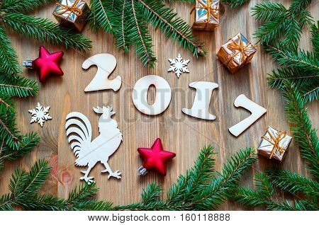 Happy New Year 2017 background with 2017 figures Christmas toys blue fir branches and rooster- New Year 2017 symbol.Concept of Happy New Year 2017 holiday- New year of red rooster. Flat lay top view