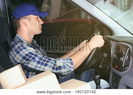Young male deliverer with boxes sitting in car