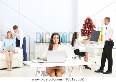Young woman working with laptop in office decorated for Christmas