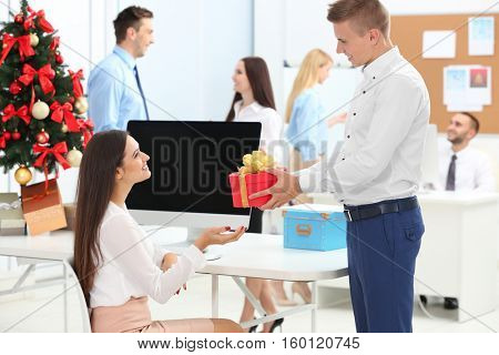 Young man giving Christmas present to his colleague in office