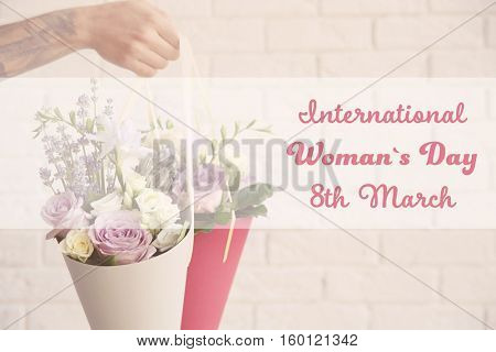 Male hand holding beautiful bouquets. Text INTERNATIONAL WOMAN'S DAY, 8TH MARCH on background