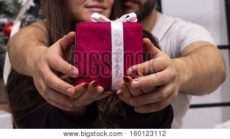 Hands of couple giving a red Christmas gift