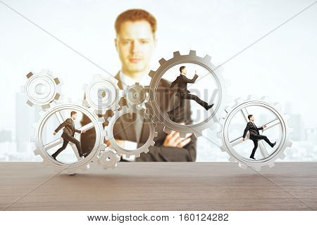 Man watching tiny businessmen running inside iron cogwheels. Teamwork and supervision concept