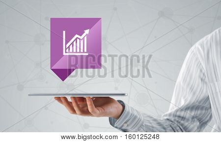Hand of businessman holding tablet pc with graph icon