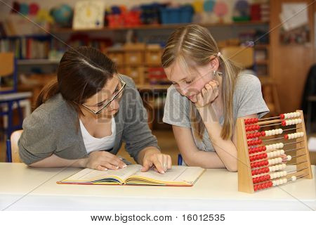 Teacher And Student In The School Textbook Learning Together