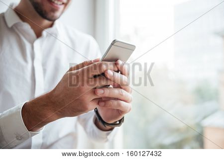 Cropped photo of businessman dressed in white shirt sitting in cafe and chatting by phone