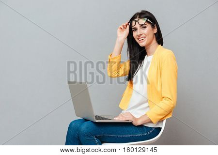 Photo of young pretty woman wearing eyeglasses and dressed in yellow jacket sitting on stool while using laptop over grey background.