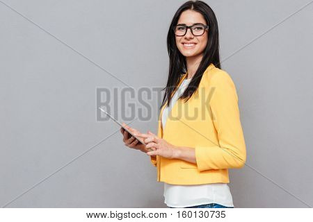 Cheerful young woman wearing eyeglasses and dressed in yellow jacket using tablet computer over grey background. Look at camera.